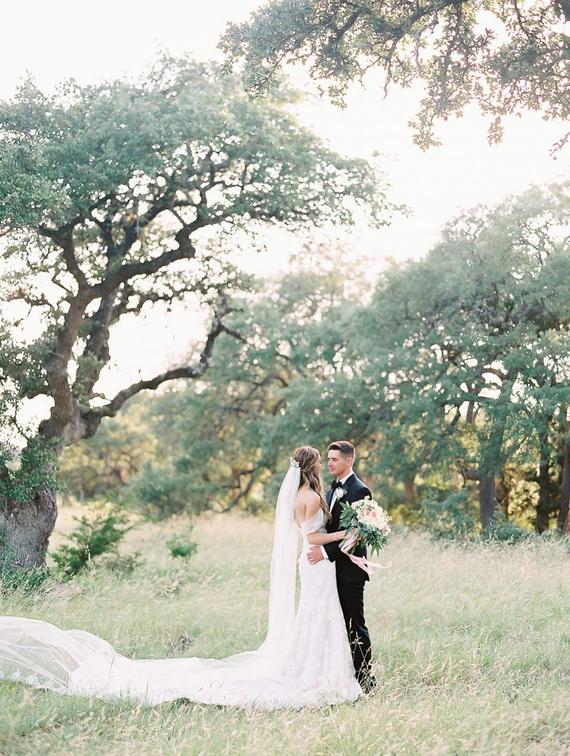 bride and groom in a field by Texas wedding photographer