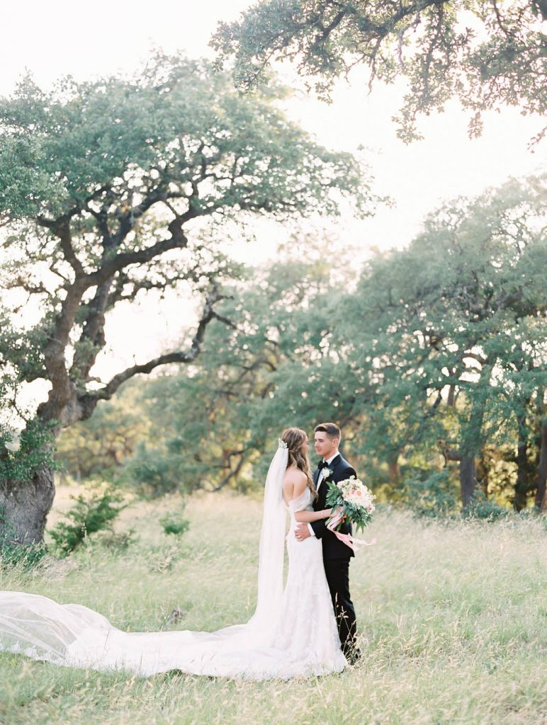 the newlyweds pose together in the texas hill country