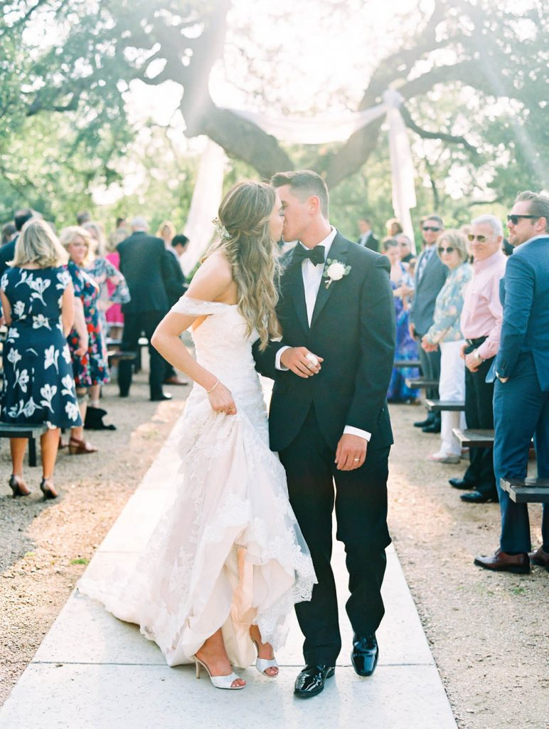 the bride and groom kiss at the end of the recessional