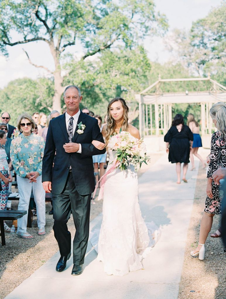 the bride walks down the aisle escorted by her father
