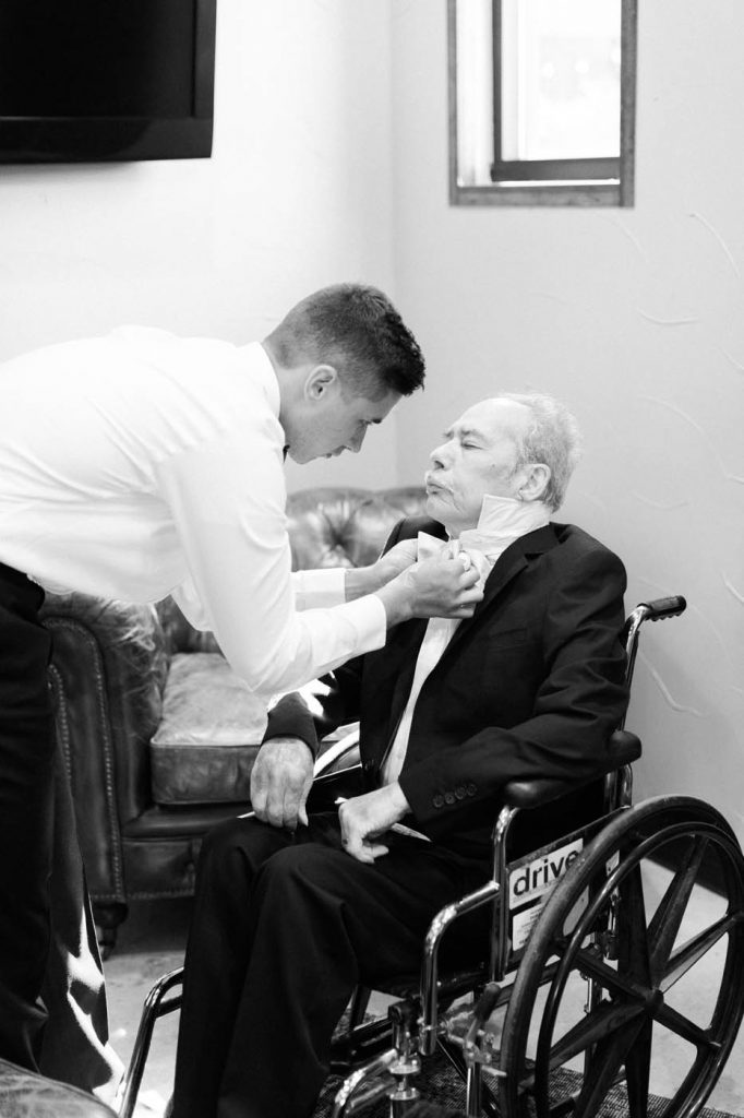 the groom helps his grandfather get ready for the wedding