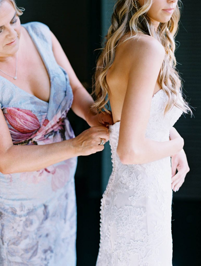 the mother of the bride zips up the bride's dress