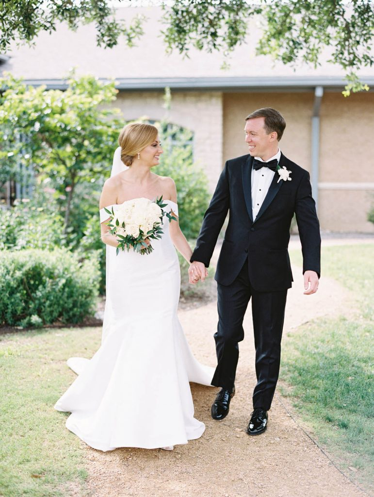the bride and groom walk together with the bridal bouquet