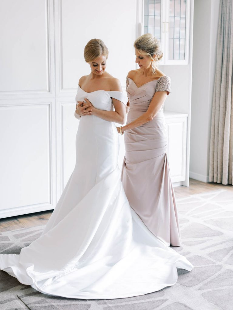 the bride's mother helps her into her Stella York dress