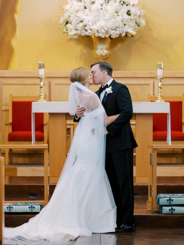 The newlyweds kiss at All Saints Chapel