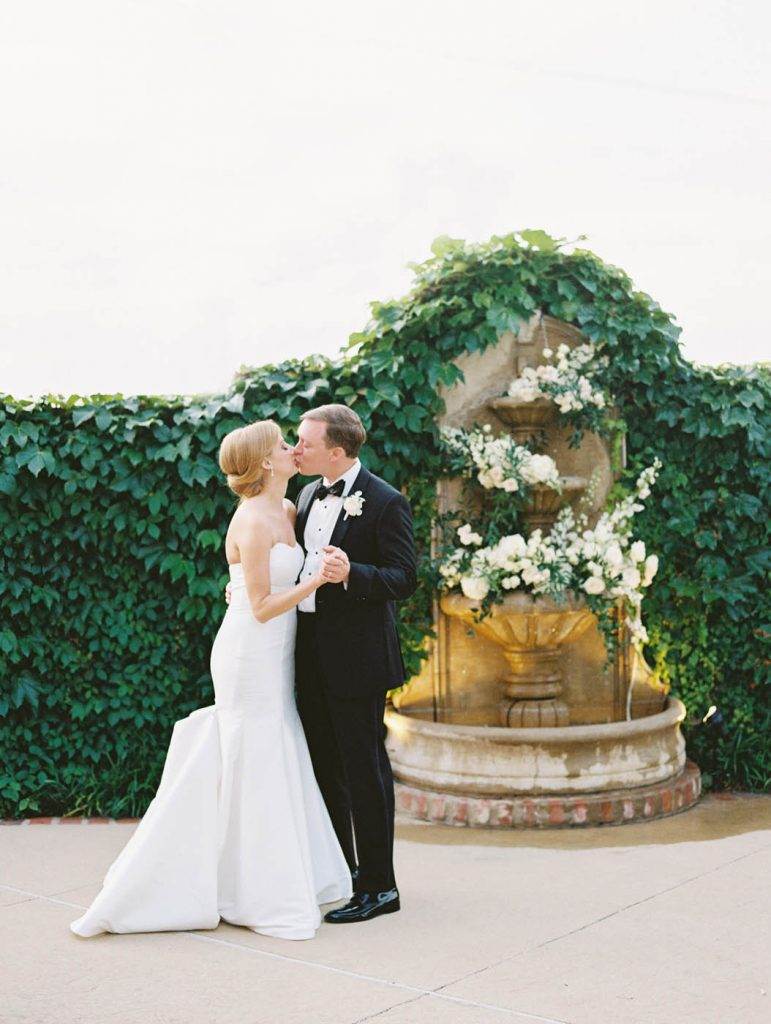 The bride and groom kiss by the fountain