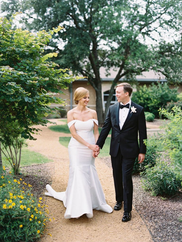 bride and groom walk together at All Saints Chapel