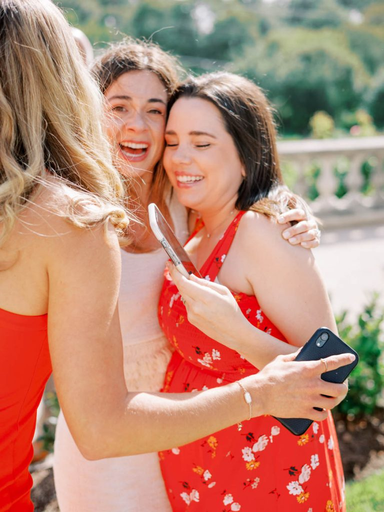 The bride hugs her friends excitedly