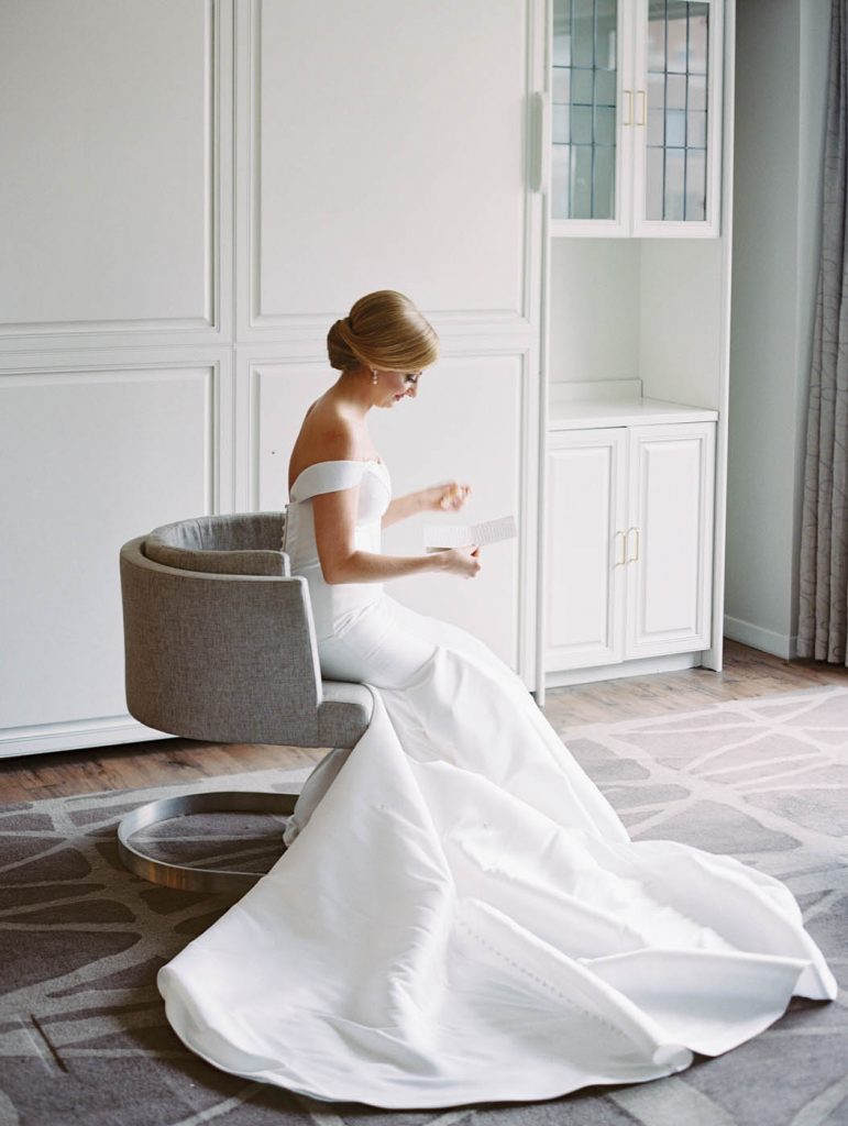 the bride reads a letter in her Stella York dress