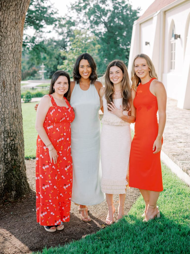 The bride shows off her ring next to friends in colorful dresses