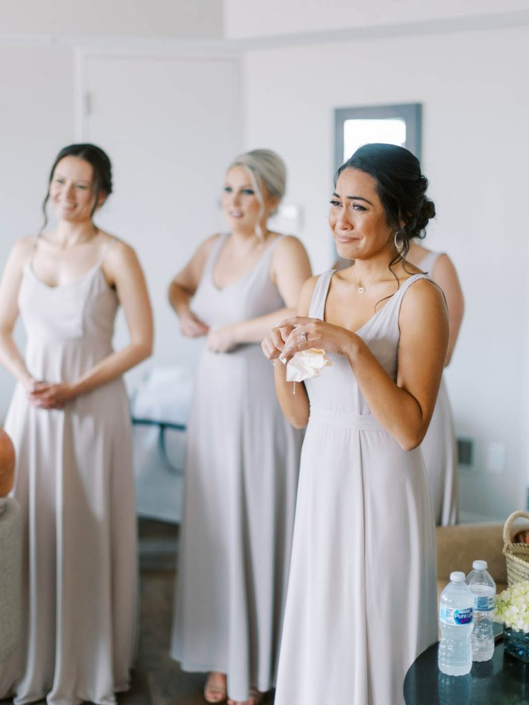 a bridesmaid gets emotional at seeing the bride fully dressed