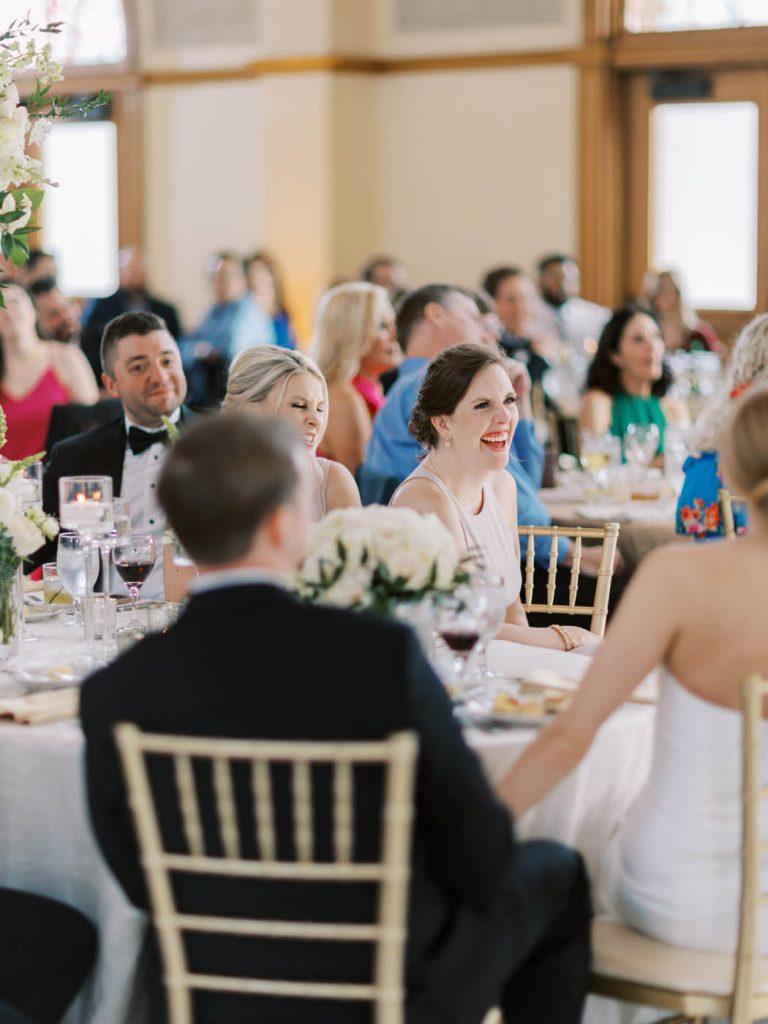 A bridesmaid laughs during a speech