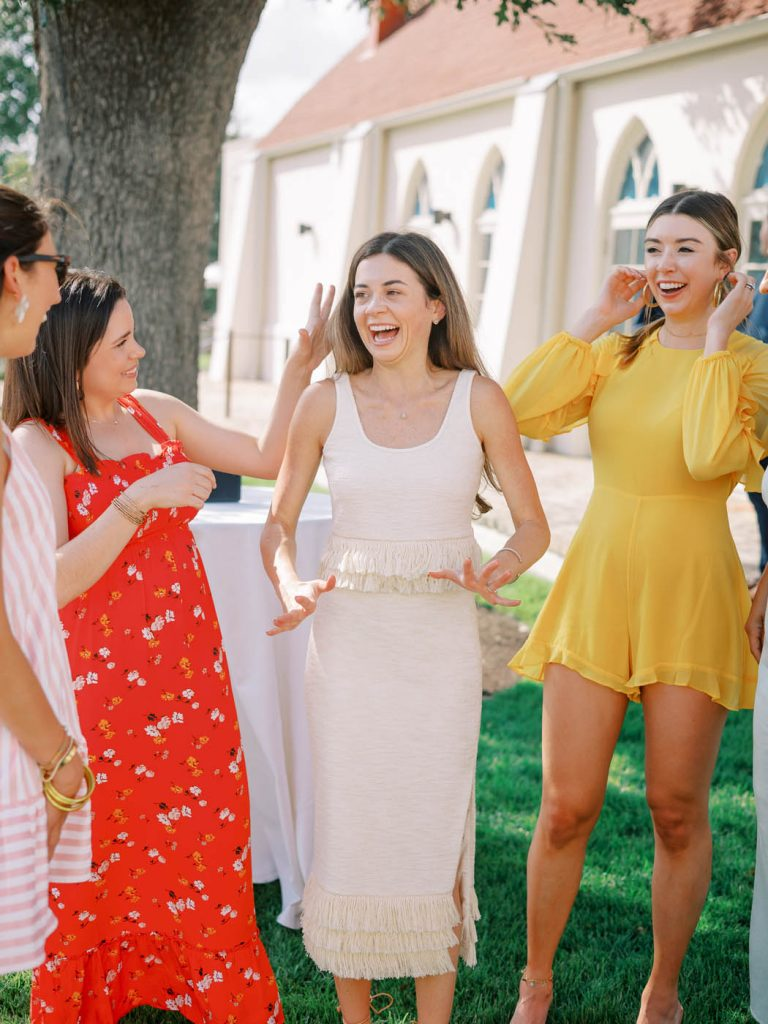 The bride stands with her friends and is excited to be engaged