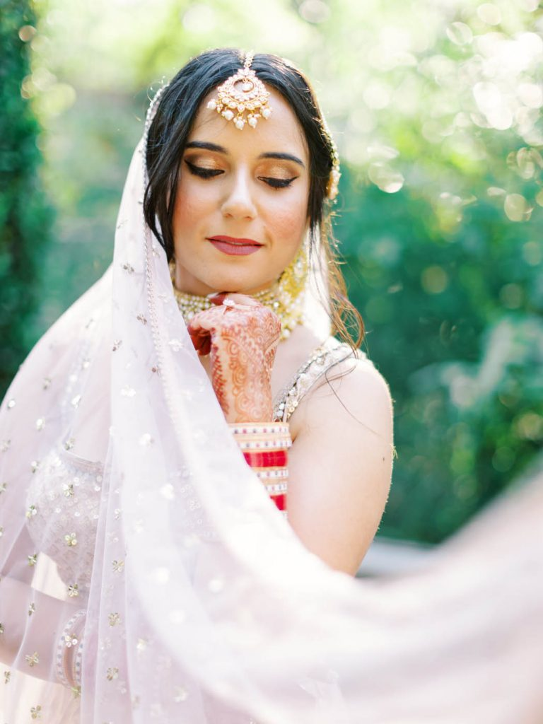 The bride poses with her draping ghoonghat