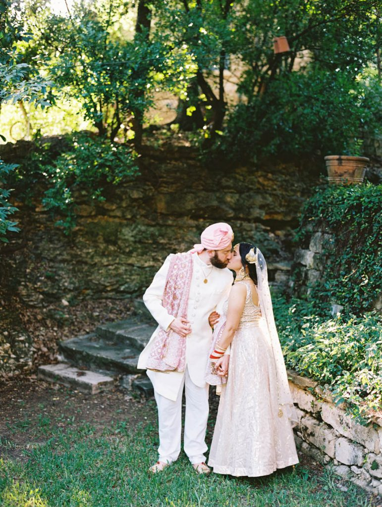 The Indian bride and groom share a kiss at Jennifer's Gardens
