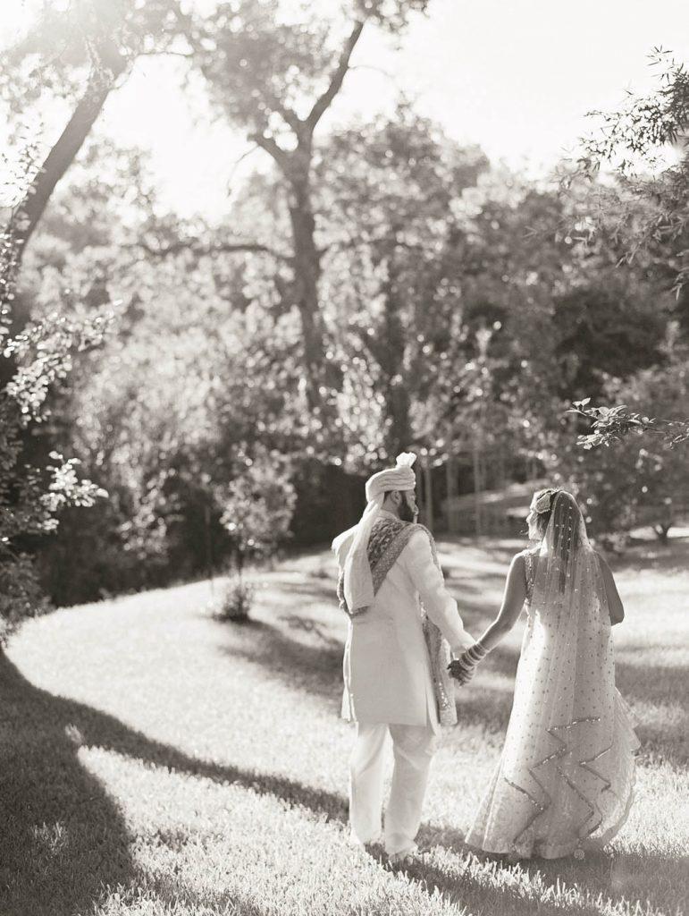 the indian bride and groom walk together at Jennifer's Gardens