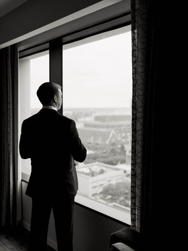 the groom looks out the window of the Worthington Renaissance in Fort Worth