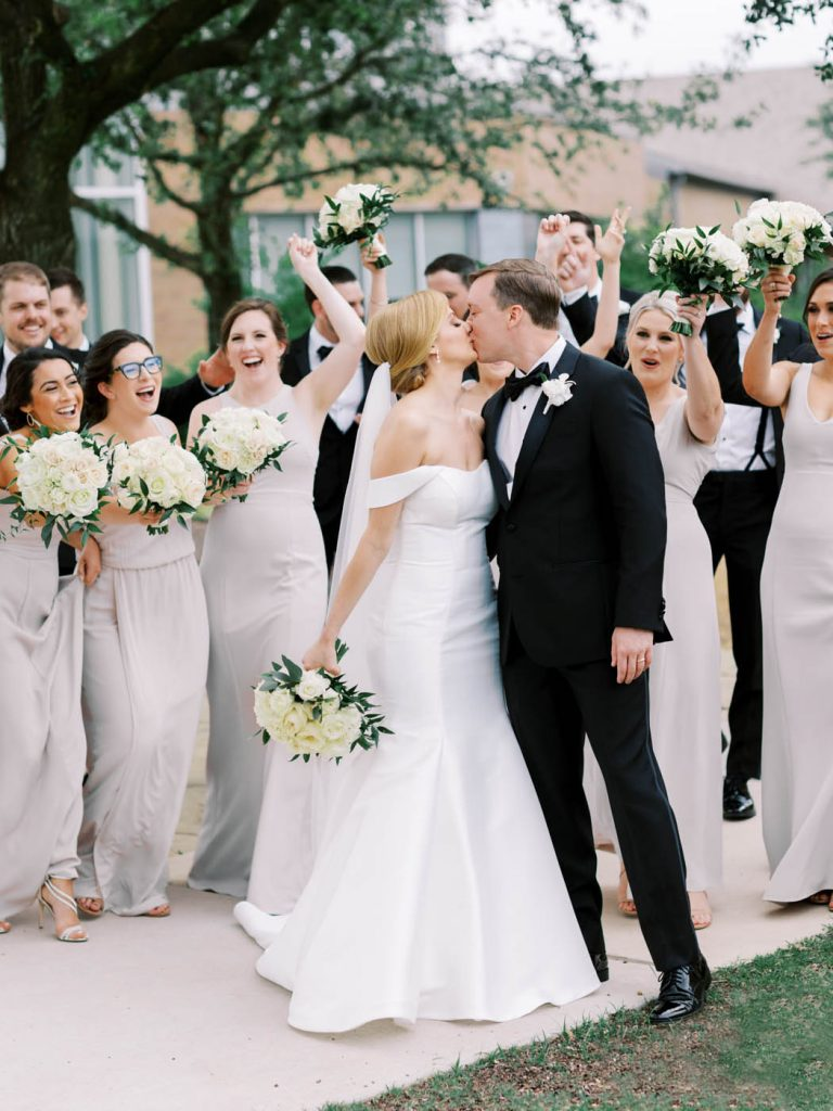 the wedding party cheers as the couple kisses